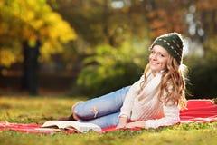 Mujer joven que lee un libro en el parque Fotos de archivo