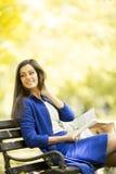 Mujer joven que lee un libro en el parque fotografía de archivo libre de regalías