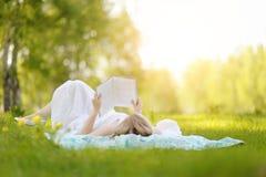 Mujer joven que lee un libro en el parque Imagen de archivo