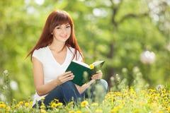 Mujer joven que lee un libro en el parque con las flores Fotos de archivo