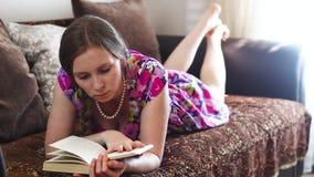 Mujer joven que lee un libro en el sofá almacen de video