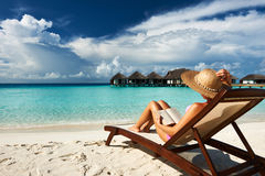 Mujer joven que lee un libro en la playa Foto de archivo