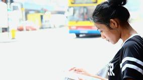 Mujer joven que lee un libro en las calles metrajes