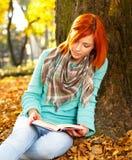 Mujer joven que lee un libro en naturaleza Imagen de archivo libre de regalías