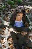 Mujer joven que lee un libro en otoño Imágenes de archivo libres de regalías