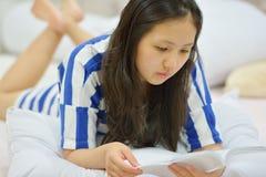 Mujer joven que lee un libro en su cama Imágenes de archivo libres de regalías