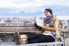 Mujer joven que lee un libro en un fondo del paisaje urbano Imagenes de archivo