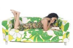 Mujer joven que lee un libro en una butaca Fotos de archivo libres de regalías