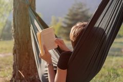 Mujer joven que lee un libro en una hamaca durante puesta del sol imágenes de archivo libres de regalías