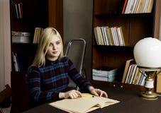 Mujer joven que lee un libro grande en biblioteca Estantes con los libros Imágenes de archivo libres de regalías