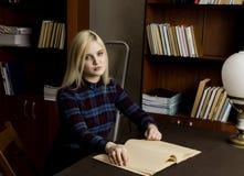 Mujer joven que lee un libro grande en biblioteca Estantes con los libros Fotografía de archivo