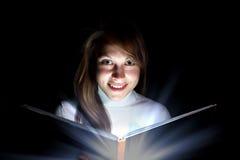 Mujer joven que lee un libro mágico Fotos de archivo