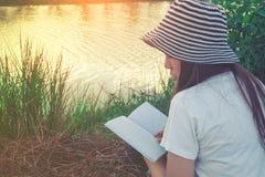 Mujer joven que lee un libro que miente en la relajación en el parque Fotos de archivo