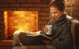 Mujer joven que lee un libro por la chimenea en un evenin del invierno foto de archivo libre de regalías