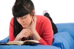 Mujer joven que lee un libro que se sienta en cama Foto de archivo libre de regalías