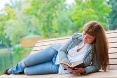 Mujer joven que lee un libro que se sienta en el banco Fotografía de archivo libre de regalías