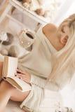Mujer joven que lee un libro y que bebe el café Imagenes de archivo