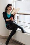 Mujer joven que lee un libro y smilling Fotos de archivo