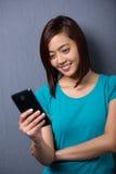 Mujer joven que lee un mensaje de texto en su móvil Imágenes de archivo libres de regalías
