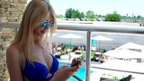 Mujer joven que lee un mensaje en el hotel almacen de metraje de vídeo