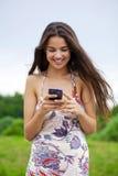 Mujer joven que lee un mensaje en el teléfono Fotografía de archivo libre de regalías