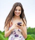 Mujer joven que lee un mensaje en el teléfono Imagen de archivo libre de regalías