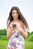 Mujer joven que lee un mensaje en el teléfono Imagen de archivo