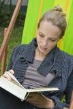 Mujer joven que lee una novela Fotos de archivo