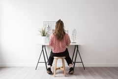 Mujer joven que lee una revista en un cuarto blanco moderno Fotografía de archivo libre de regalías