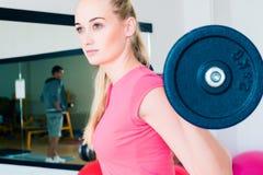 Mujer joven que levanta un barbell en el gimnasio Fotos de archivo libres de regalías