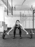 Mujer joven que levanta un barbell en un gimnasio del crossfit Fotografía de archivo libre de regalías