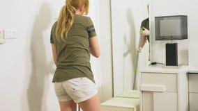 Mujer joven que limpia el dormitorio con los productos de limpieza y el equipo, concepto del quehacer doméstico almacen de video