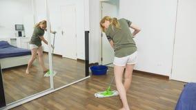 Mujer joven que limpia el dormitorio con los productos de limpieza y el equipo, concepto del quehacer doméstico metrajes
