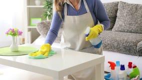 Mujer joven que limpia el primer de la tabla