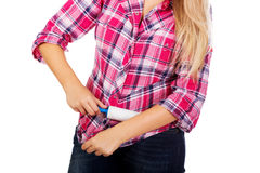 Mujer joven que limpia su camisa con el rodillo de la pelusa Fotografía de archivo libre de regalías