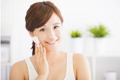 mujer joven que limpia su cara con algodón fotos de archivo libres de regalías