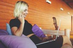 Mujer joven que llama vía el teléfono móvil mientras que usa el ordenador portátil foto de archivo libre de regalías