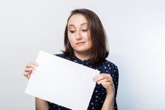 Mujer joven que lleva a cabo al tablero del negocio de la muestra, en blanco sobre el fondo blanco, imagen de archivo libre de regalías