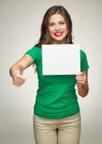 Mujer joven que lleva a cabo al tablero del negocio de la muestra que muestra el pulgar para arriba Imagenes de archivo