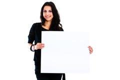 Mujer joven que lleva a cabo al tablero en blanco Foto de archivo