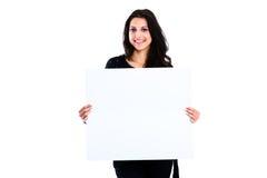 Mujer joven que lleva a cabo al tablero en blanco Fotografía de archivo
