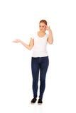 Mujer joven que lleva a cabo algo en la palma abierta y que piensa en algo Imagenes de archivo