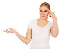 Mujer joven que lleva a cabo algo en la palma abierta y que piensa en algo Foto de archivo libre de regalías