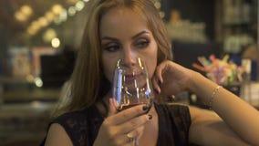Mujer joven que lleva a cabo el aroma rojo disponible de la copa de vino y el oler en restaurante Mujer que prueba y que bebe el  almacen de metraje de vídeo
