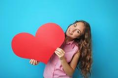 Mujer joven que lleva a cabo el corazón rojo Imagen de archivo libre de regalías