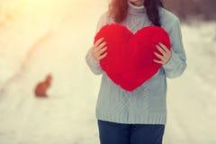 Mujer joven que lleva a cabo el corazón rojo al aire libre en invierno foto de archivo