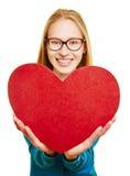 Mujer joven que lleva a cabo el corazón rojo grande Imagen de archivo