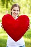 Mujer joven que lleva a cabo el corazón rojo grande Imagen de archivo libre de regalías