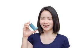 Mujer joven que lleva a cabo el dispositivo del inhalador Imagenes de archivo