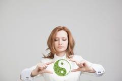 Mujer joven que lleva a cabo el símbolo ying de yang imagenes de archivo
